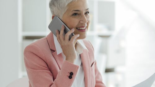 Mature businesswoman working in her new modern office. Sitting by the desk and talking on the phone with client. She is happy and cheerful. Holding papers in the hand.